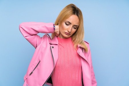 Young blonde woman with pink jacket over isolated blue background with neckache