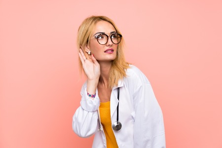 Young blonde doctor woman listening something