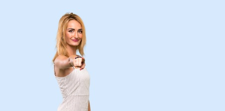 Young blonde woman points finger at you with a confident expression over isolated blue background