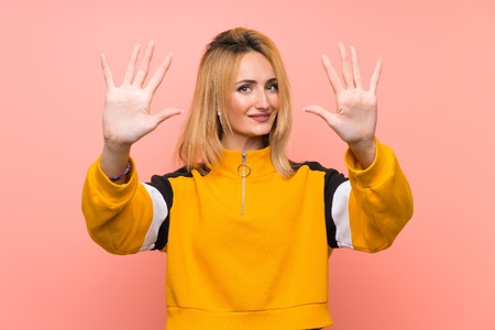 Young blonde woman over isolated pink background counting ten with fingers Banco de Imagens