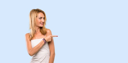 Young blonde woman pointing finger to the side over isolated blue background