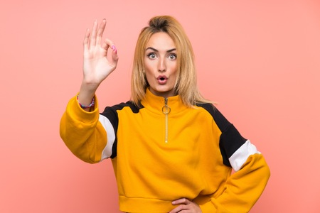Young blonde woman over isolated pink background surprised and showing ok sign