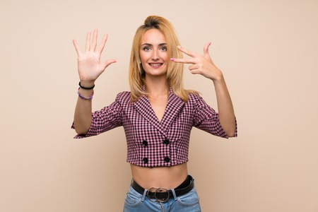 Young blonde woman with pink jacket over isolated wall counting eight with fingers Banco de Imagens