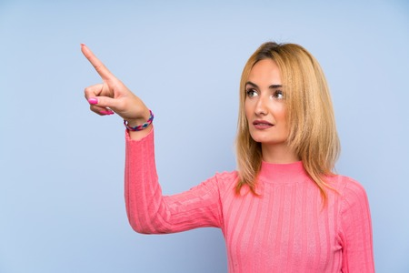 Young blonde woman with pink sweater over isolated blue background touching on transparent screen