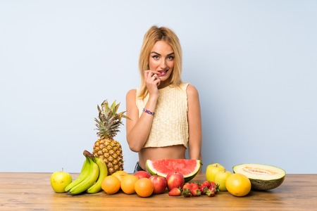 Young blonde woman with lots of fruits nervous and scared Stock Photo