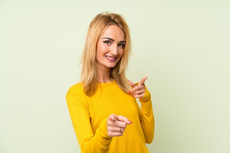 Young blonde woman over isolated green background points finger at you