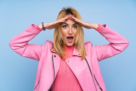 Young blonde woman with pink jacket over isolated blue background with surprise expression