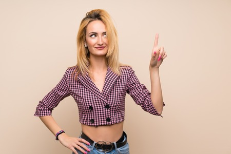 Young blonde woman with pink jacket over isolated wall showing and lifting a finger in sign of the best