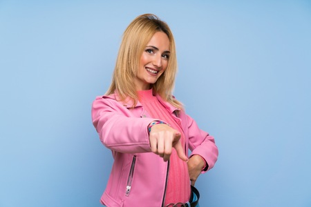 Young blonde woman with pink jacket over isolated blue background points finger at you with a confident expression Stock Photo