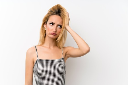 Young blonde woman over isolated white with an expression of frustration and not understanding