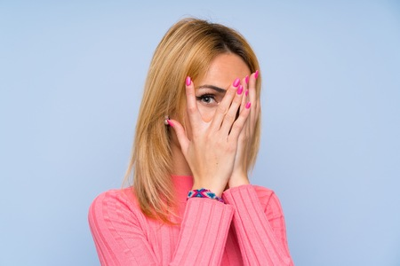 Young blonde woman with pink sweater over isolated blue background covering eyes and looking through fingers