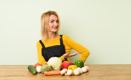 Young blonde woman with lots of vegetables extending hands to the side for inviting to come