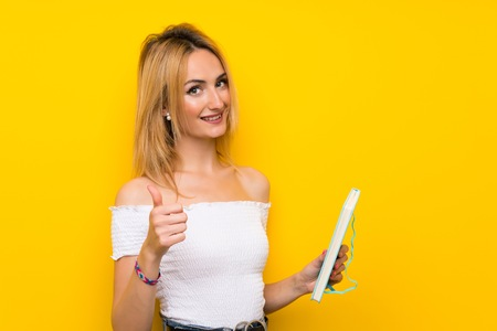 Young blonde woman over isolated yellow wall holding and reading a book