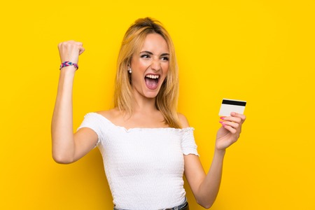 Young blonde woman over isolated yellow wall holding a credit card Stock Photo