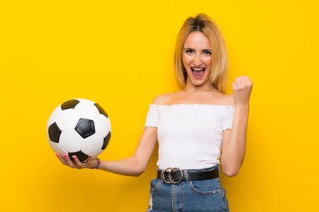 Young blonde woman over isolated yellow wall holding a soccer ball Stock Photo