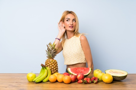 Young blonde woman with lots of fruits listening something Stock Photo