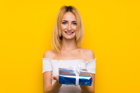 Young blonde woman over isolated yellow wall holding gift box
