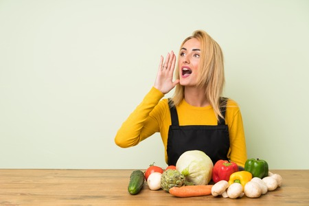 Young blonde woman with lots of vegetables shouting with mouth wide open