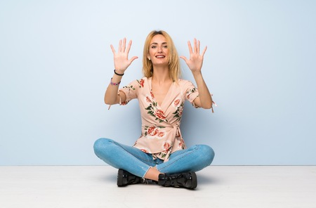 Young blonde woman sitting on the floor counting ten with fingers Stockfoto