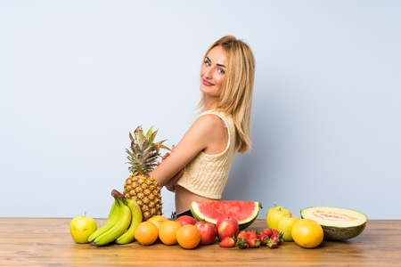 Young blonde woman with lots of fruits laughing Stock Photo