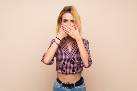 Young blonde woman with pink jacket over isolated wall covering mouth with hands