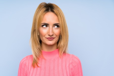 Young blonde woman with pink sweater over isolated blue background standing and looking to the side