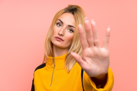 Young blonde woman over isolated pink background making stop gesture Stockfoto