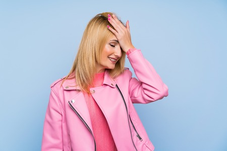 Young blonde woman with pink jacket over isolated blue background has realized something and intending the solution