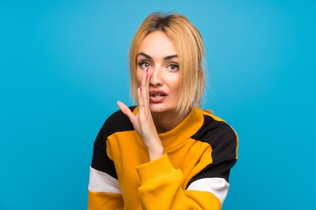 Young blonde woman over isolated blue background whispering something