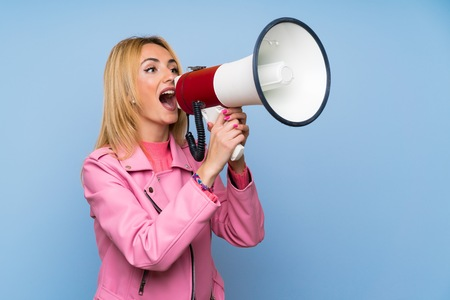 Young blonde woman with pink jacket over isolated blue background shouting through a megaphone Stock Photo