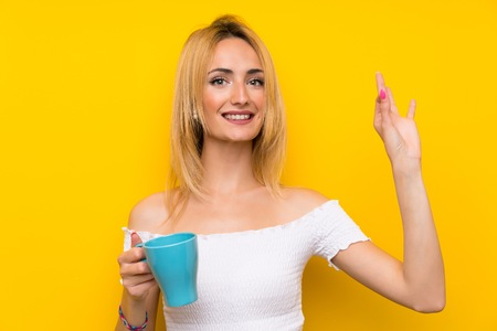 Young blonde woman over isolated yellow wall holding hot cup of coffee