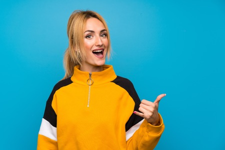 Young blonde woman over isolated blue background making phone gesture