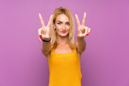 Young blonde woman over purple background smiling and showing victory sign