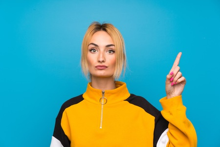 Young blonde woman over isolated blue background pointing with the index finger a great idea