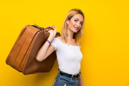 Young blonde woman over isolated yellow wall holding a vintage briefcase 版權商用圖片 - 124773326