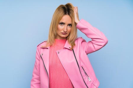 Young blonde woman with pink jacket over isolated blue background with an expression of frustration and not understanding