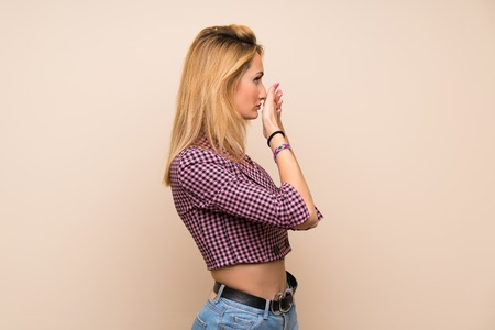 Young blonde woman with pink jacket over isolated wall covering mouth and looking to the side