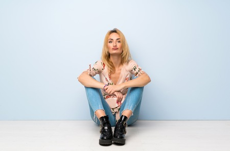 Young blonde woman sitting on the floor portrait