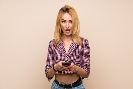 Young blonde woman with pink jacket over isolated wall surprised and sending a message