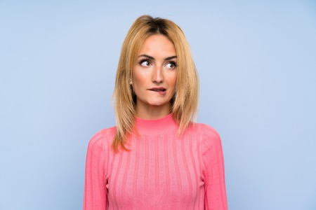 Young blonde woman with pink sweater over isolated blue background having doubts and with confuse face expression