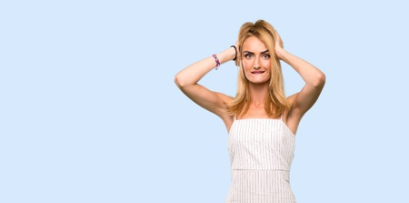Young blonde woman frustrated and takes hands on head over isolated blue background