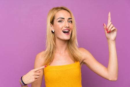 Young blonde woman over purple background with surprise facial expression