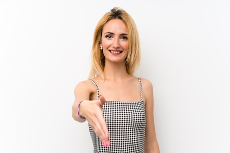 Young blonde woman over isolated white shaking hands for closing a good deal