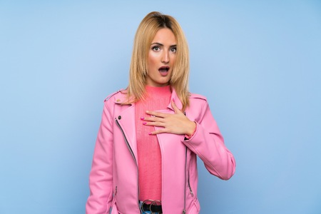 Young blonde woman with pink jacket over isolated blue background surprised and shocked while looking right