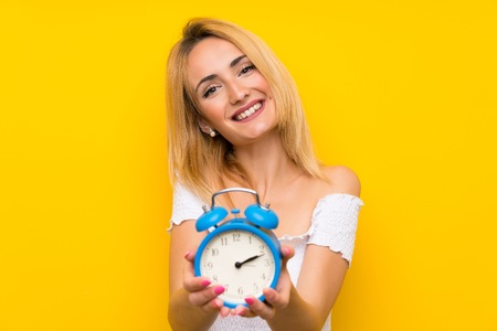 Young blonde woman over isolated yellow wall holding vintage alarm clock Stock Photo