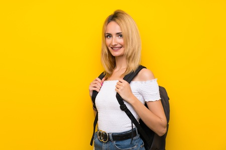 Young blonde woman over isolated yellow wall with backpack Imagens
