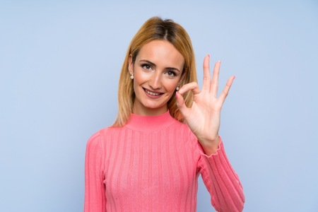 Young blonde woman with pink sweater over isolated blue background showing an ok sign with fingers