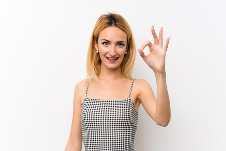 Young blonde woman over isolated white showing ok sign with fingers