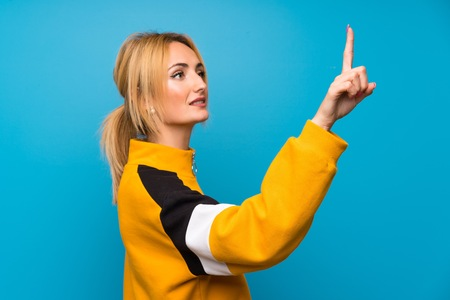 Young blonde woman over isolated blue background touching on transparent screen Stockfoto