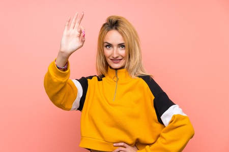 Young blonde woman over isolated pink background showing ok sign with fingers